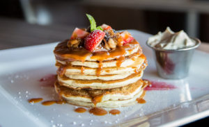 gingerbread pancakes topped with strawberries and syrup